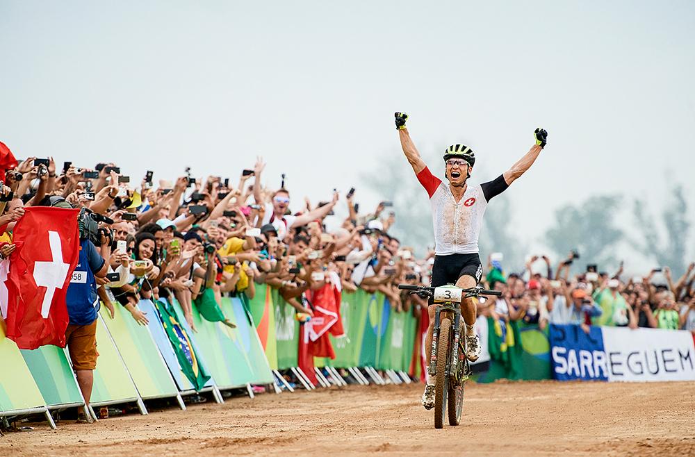 来自瑞士的Nino Schurter在2016年里约奥运会男子山地自行车比赛的终点庆祝胜利。
