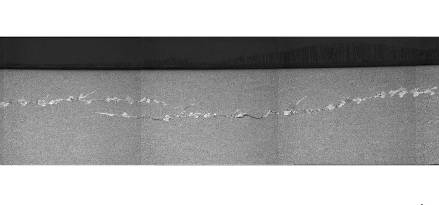 Обширная подповерхностная сеть белых трещин травления на наружном кольце подшипника 23024, вызванная кратковременным воздействием тяжёлых нагрузок.